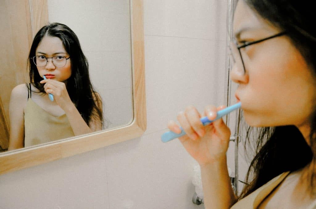 woman brushes teeth in front of mirror