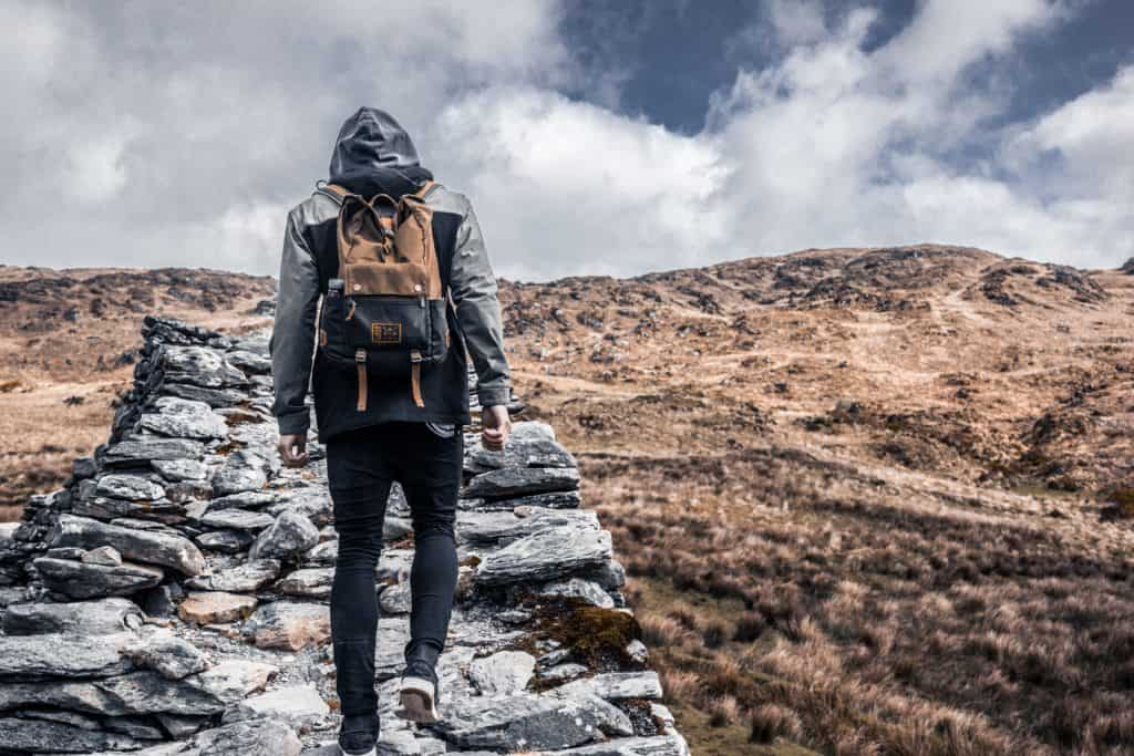 hiking up a mountain stone path backpack