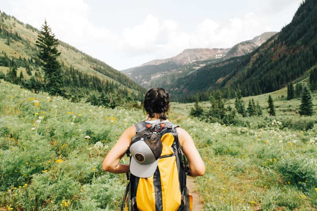 woman hiking in green valley backpack