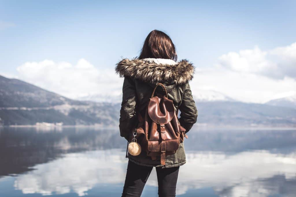 woman standing in front of lake leather backpack